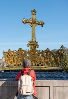 Chłopiec szuka złotego krzyża i korony w lourdes, francja, hautes pyrenees