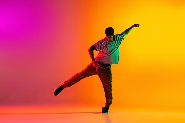 Chłopiec tańczy hip-hop w stylowe ubrania na gradientowym tle w sali tanecznej w neonowym świetle.