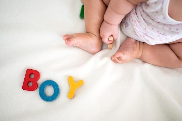 Chłopiec tekst drewniane słowo na koc z niewyraźne dziecko stóp i kopia tło