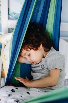 Chłopiec tęskni za domem bawić się telefonu obsiadanie w hamaku