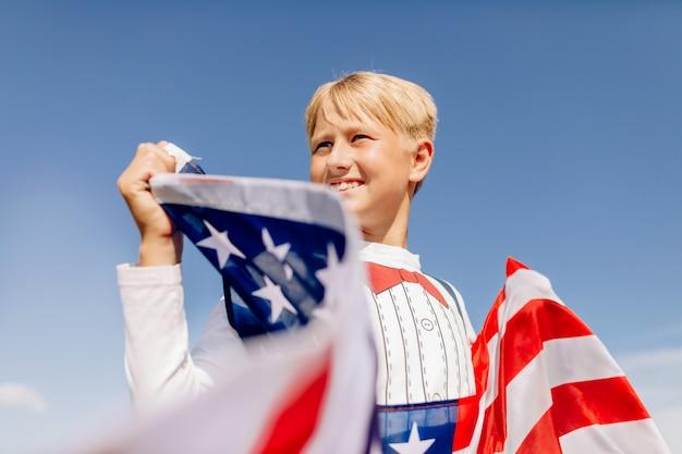 Chłopiec trzyma amerykańską flagę. patrioci ameryki.