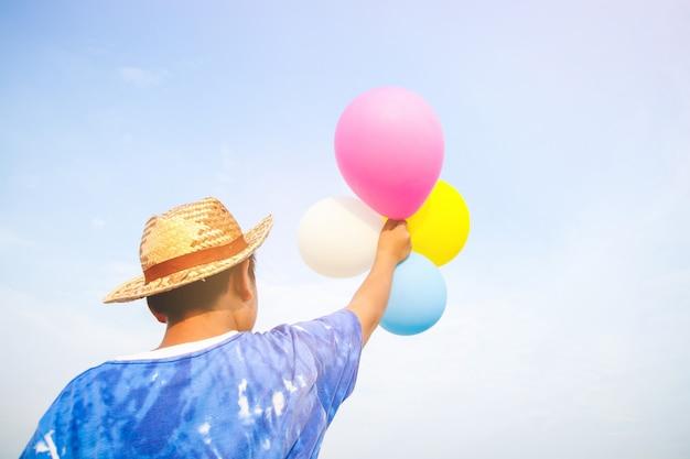 Chłopiec trzyma balon w kolorze niebieskim, białym, różowym i fioletowym i unosi ręce na niebie.