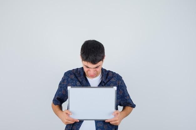 Chłopiec trzyma białą tablicę, patrząc na nią w białej koszulce, kwiecistej koszuli i wygląda ponuro. przedni widok.