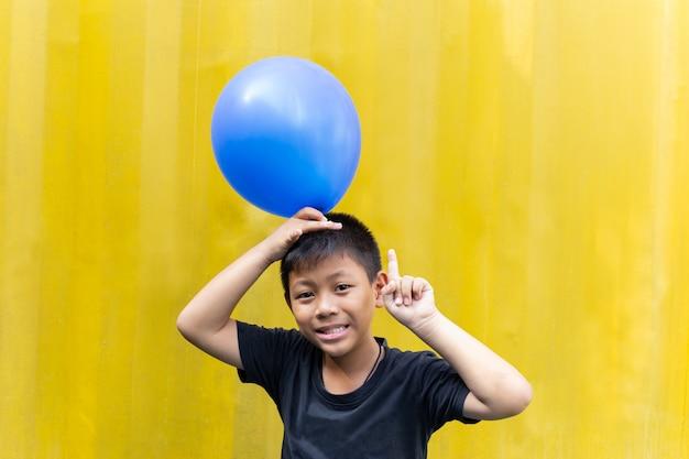 Chłopiec trzyma błękit szybko się zwiększać pozycję na żółtym tle.