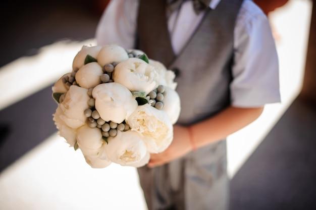 Chłopiec trzyma bukiet ślubny z białych róż w kształcie pionu i brunii