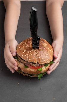 Chłopiec trzyma burgera. zbliżenie domowy wegański burger z cebulą i warzywami podany z nożem.