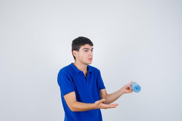 Chłopiec trzyma butelkę wody, wyciągając rękę, przedstawiając ją w niebieskim t-shircie i wyglądając na zaskoczonego. przedni widok.