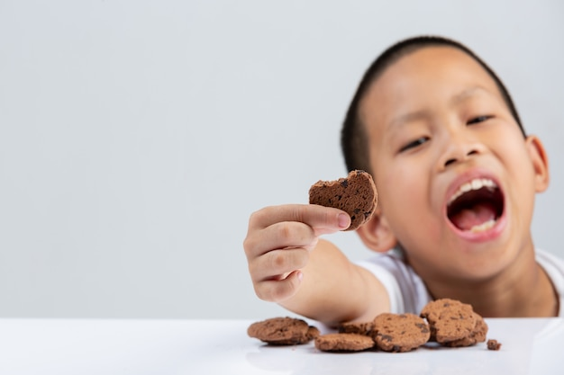 Chłopiec trzyma ciastka chce jeść przy stołem na biel ścianie.