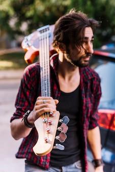 Chłopiec trzyma gitarę elektryczną