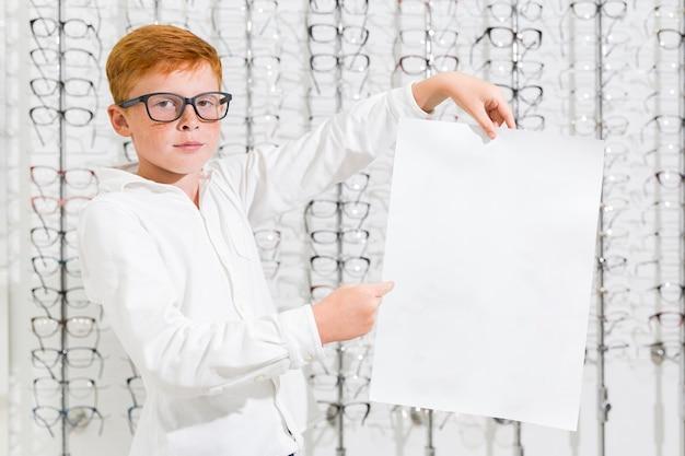 Chłopiec trzyma i wskazuje przy czarnym białym papierem w optyka sklepie