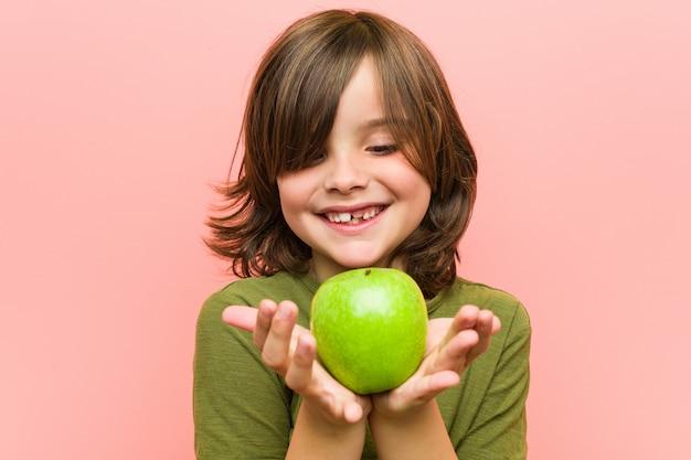 Chłopiec trzyma jabłka