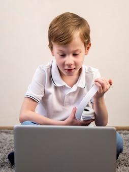 Chłopiec trzyma jego hełmofony