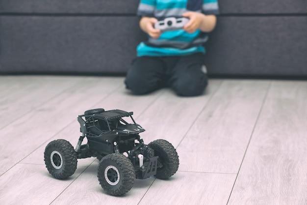 Chłopiec trzyma joystick i bawi się radiowym samochodem