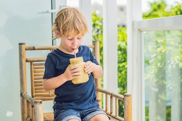 Chłopiec trzyma koktajl bananowy, koncepcja prawidłowego odżywiania.