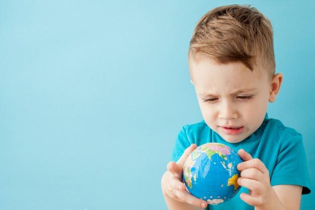 Chłopiec trzyma kulę ziemską na błękitnym tle