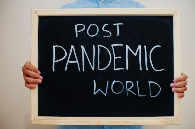 Chłopiec trzyma na tablicy napis z tekstem post pandemic world