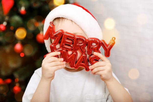 Chłopiec trzyma napis wesołych świąt bożego narodzenia