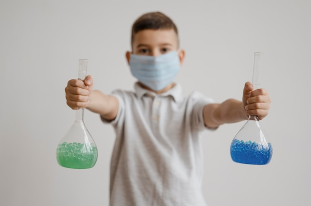 Chłopiec trzyma pierwiastki chemiczne w odbiorcach