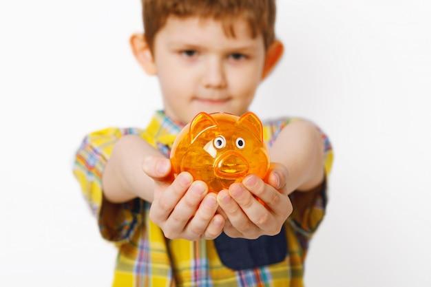 Chłopiec trzyma piggybank w rękach.