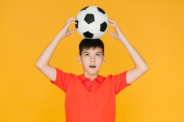 Chłopiec trzyma piłkę do piłki nożnej na głowie