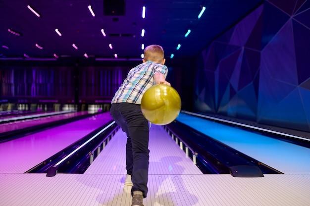 Chłopiec trzyma piłkę na torze w kręgielni. dzieciak przygotowuje się do zdobycia strajku. dzieci bawiące się w centrum rozrywki, dziecko melonik