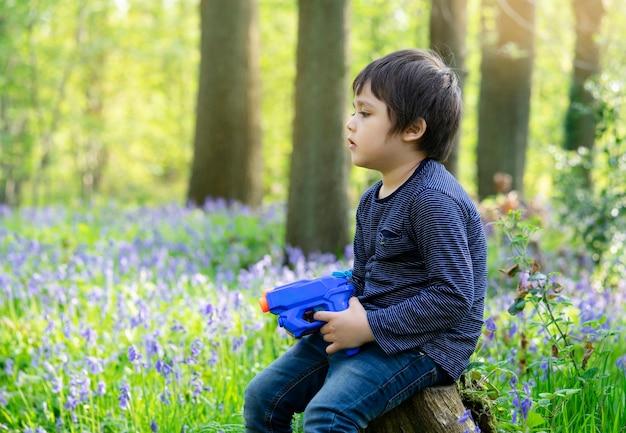 Chłopiec trzyma plastikowego pistoletu wodnego