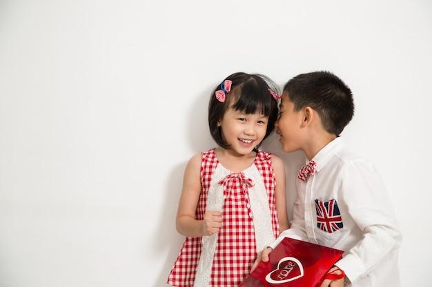 Chłopiec trzyma prezent na prezent dla dziewczyny z białym tłem.