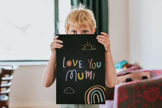 Chłopiec trzyma pustą czarną tablicę, kocham cię mamo tekst