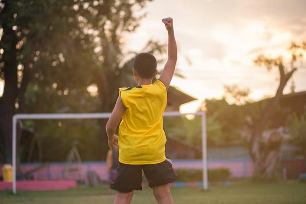 Chłopiec trzyma ręce wyświetlono zwycięstwo w piłce nożnej.
