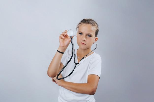 Chłopiec trzyma stetoskop w dłoniach na pojedyncze światło