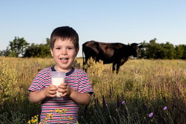 Chłopiec trzyma szklankę mleka i uśmiecha się w polu.