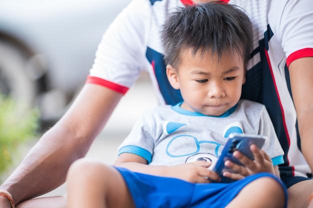 Chłopiec trzyma telefon komórkowy siedzi na kolanach taty
