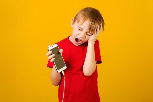 Chłopiec trzyma telefon z uszkodzonym przewodem do ładowania.