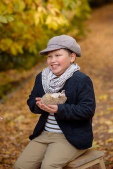 Chłopiec trzyma w rękach dorosłego jeża na tle jesiennego lasu