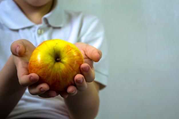 Chłopiec trzyma w rękach jabłko na białym tle