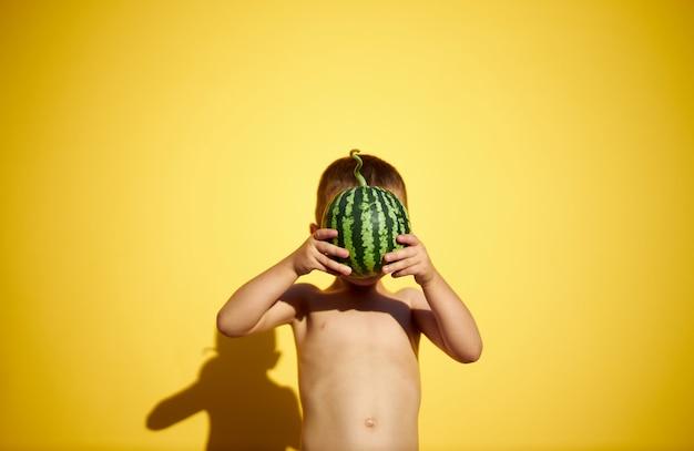 Chłopiec trzyma w rękach małego arbuza