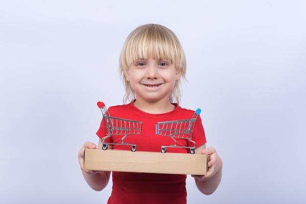 Chłopiec trzyma w rękach pudełko i dwa wózek na zakupy
