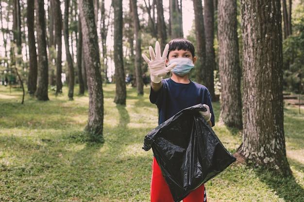 Chłopiec trzyma worek na śmieci z ręką gest zatrzymania w lesie