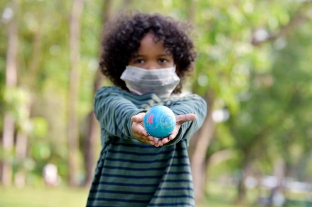 Chłopiec trzyma ziemię w ręce i nosi maskę ochronną medycznych