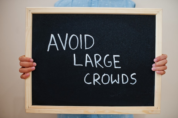 Chłopiec trzymaj napis na tablicy, unikając dużych tłumów