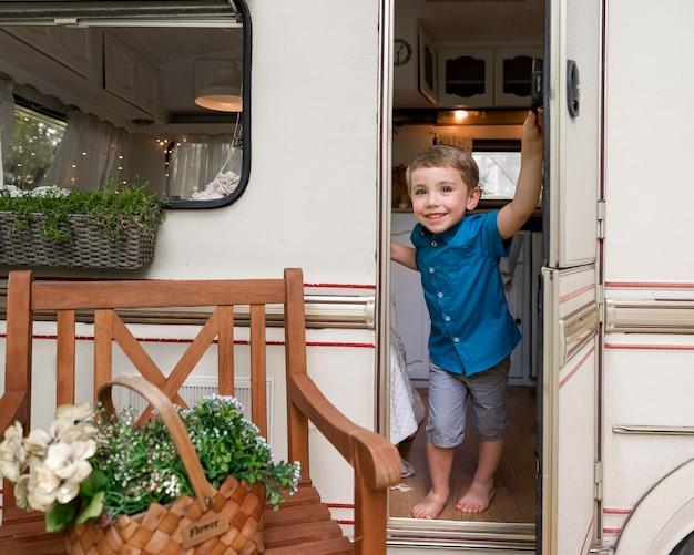 Chłopiec trzymający drzwi swojej przyczepy kempingowej