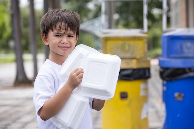 Chłopiec trzymający styropianowe pudełko do wyrzucenia do kosza