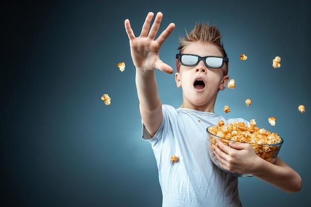 Chłopiec trzymający w rękach popcorn oglądający film w okularach 3d, strach, niebieska ściana. pojęcie kina, filmu, emocji, niespodzianki, rozrywki. platformy przesyłania strumieniowego.