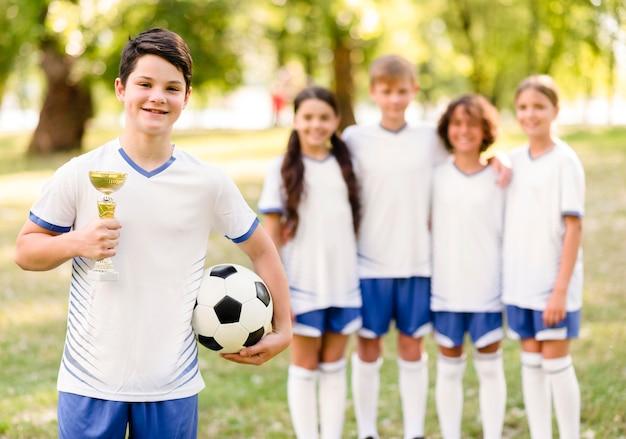 Chłopiec trzymający złote trofeum obok kolegów z drużyny