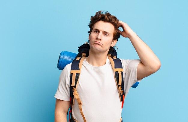 Chłopiec turysta czuje się zakłopotany i zdezorientowany, drapiąc się po głowie i patrząc w bok