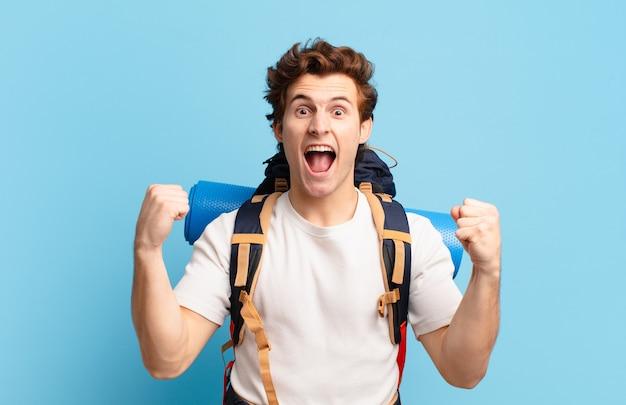Chłopiec turysta krzyczy agresywnie z gniewnym wyrazem twarzy lub z zaciśniętymi pięściami świętuje sukces