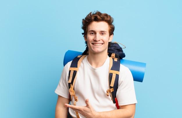 Chłopiec turysta uśmiecha się radośnie, czuje się szczęśliwy i pokazuje koncepcję w przestrzeni kopii z dłonią palm