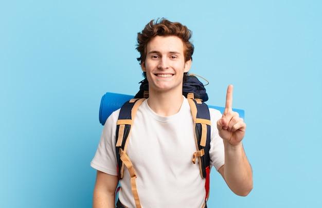 Chłopiec turysta uśmiechnięty i wyglądający przyjaźnie, pokazujący numer jeden lub pierwszy z ręką do przodu, odliczający w dół
