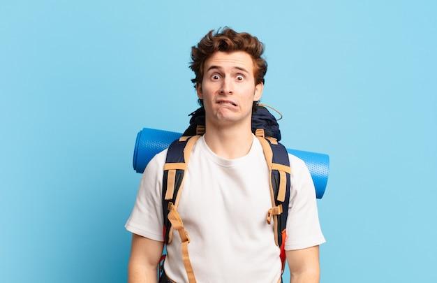 Chłopiec turysta wyglądający na zdziwionego i zdezorientowanego, przygryzający wargę nerwowym gestem, nie znający odpowiedzi na problem
