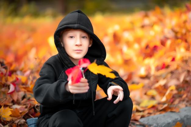 Chłopiec ubrany w czarną kurtkę z kapturem trzyma w dłoni jesienny liść.